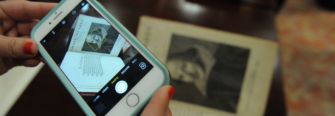 A student taking a photo of the First Folio